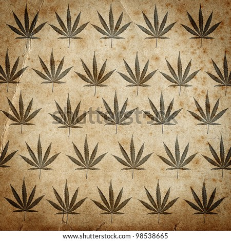 Grungy old paper background with cannabis leaves