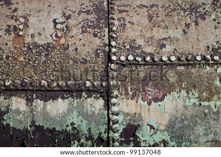 Grungy old riveted metal plates covered in flaking paint
