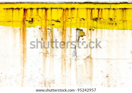 Grungy old wall with peeling yellow paint and dripping rusty lines creates unique background texture.