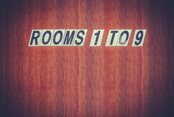 Grungy Retro Sign For Rooms On An Old Wooden Door At A Hotel, Motel, Boarding House, Hostel Or Bedsit