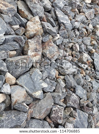 Grungy rocky boulder hill slope in a stone quarry mine for textural background.