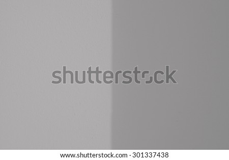 Grungy rough cast wall background texture with contrasting fields in light and shadow.
