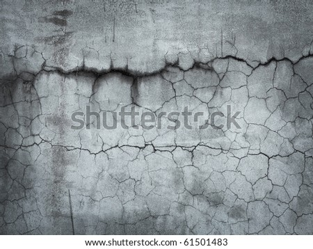 Grungy stone wall with many cracks.