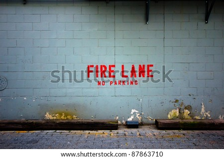 "Grungy urban alley wall with the words ""fire lane"" posted"
