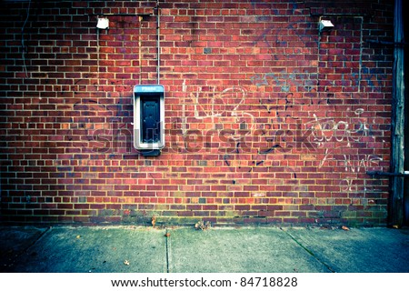 Grungy urban background of a brick wall with an old out of service payphone on it