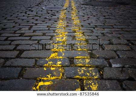 Grungy urban image of New York City cobblestone street and yellow lines