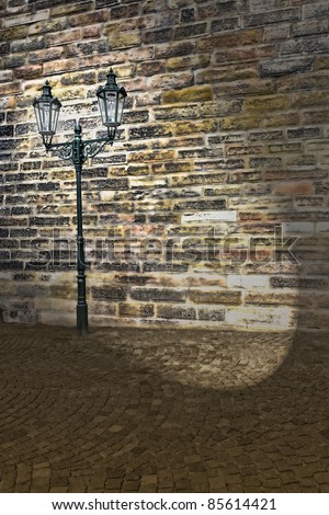 grungy wall and streetlamp at night shedding spotlight