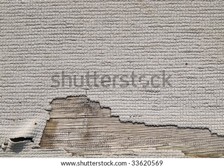 Grungy wall paper texture. Torn and aged white wallpaper on wood.