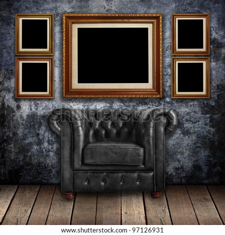 Grungy wall with Classic Brown leather armchair and gold frames background.