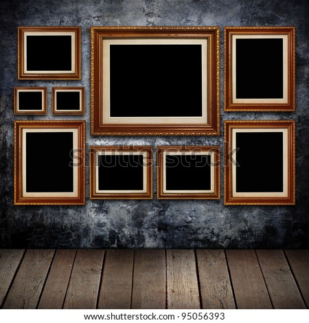 Grungy wall with gold frames and old wood background.