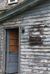 Grungy, weathered, ruined abandoned home with door cracked open, ready for vagrants and squatters.  Moldy peeling paint on the siding, and boarded up, open door.  Concept:  bankruptcy, temptation.