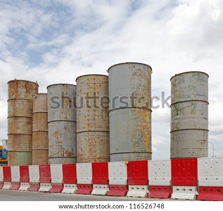 Grungy weathered steel industrial silo behind protective barrier against a blue cloudy sky