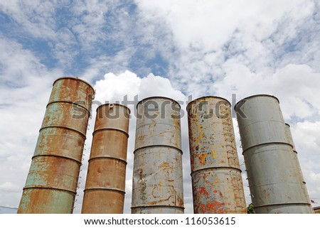 Grungy weathered steel industrial silo rising up against a blue cloudy sky for the concept of urban stonehenge.
