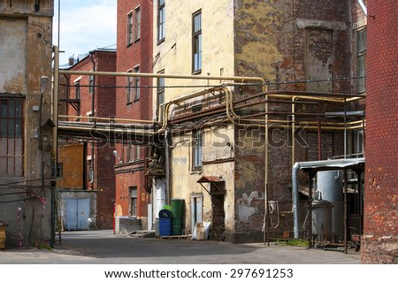 Grungy yard and residential houses of a small factory in big city of Russia #297691253