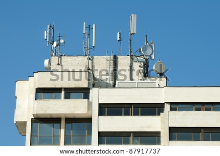 GSM transmitters on a roof of white administrative building