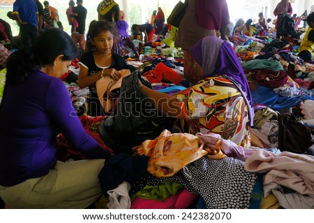 GUA MUSANG, KELANTAN - DECEMBER 31: Flood victims choosing clothes donated by people in evacuation center, Gua Musang aftermath the worst flood that ever hit Kelantan, Malaysia on December 31, 2014