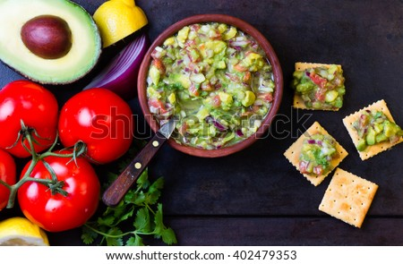 Guacamole and ingredients - avocado, tomatoes, onio, garlic, cilantro and crackers on dark still  background. Top view #402479353