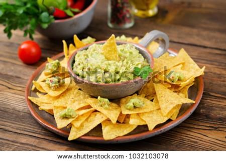 Guacamole avocado, lime, tomato, onion and cilantro, served with nachos - Traditional Mexican snack #1032103078