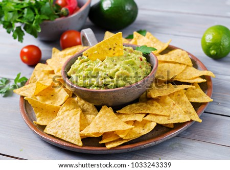 Guacamole avocado, lime, tomato, onion and cilantro, served with nachos - Traditional Mexican snack #1033243339