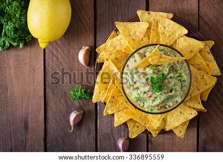 Guacamole avocado, lime, tomato, onion and cilantro, served with nachos - Traditional Mexican snack. Top view #336895559