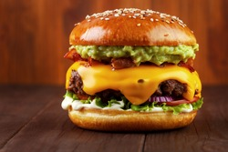 Guacamole beef burger with melted cheese and bacon on wooden background