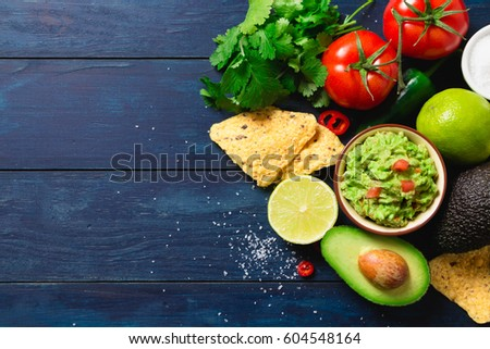 Guacamole bowl with ingredients and tortilla chips on a blue painted wooden table. Top view #604548164