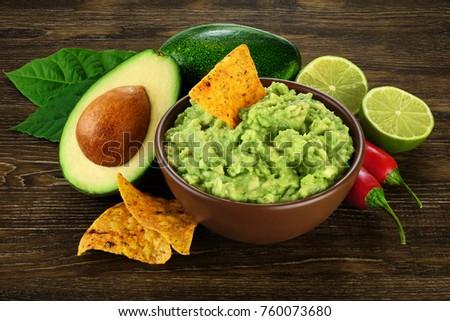 Guacamole nachos and guacamole ingredients on dark wooden background.