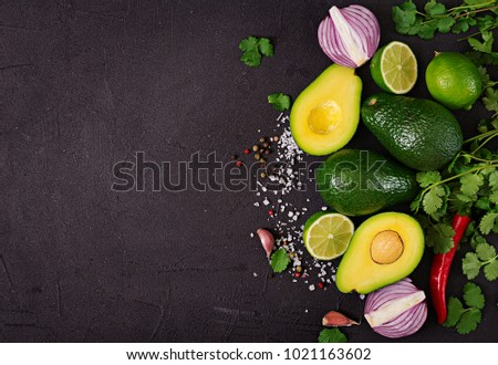 Guacamole sauce ingredients - avocado,  onion, pepper chili, garlic, cilantro, lime on black background. Top view