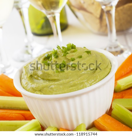 Guacamole topped with fresh green chilli, with carrot and celery sticks for dipping.