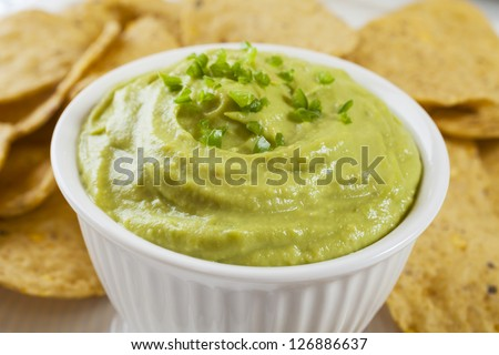 Guacamole topped with fresh green chilli, with corn chips for dipping. Shallow DF, focus on chilli.