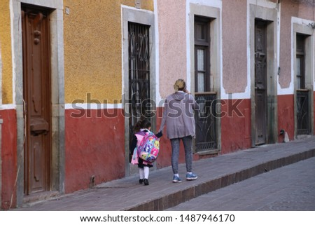 Guanajuato, Mexico - October, 2018: The people of Mexico. The town of Guanajuato Filled with its colorful streets and unique architecture. Mom and her daughter walking in the street.