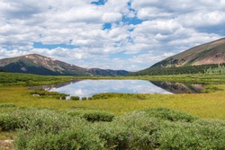 Guanella Pass high altitude landscape of pond, greenery, clouds and mountains in Colorado