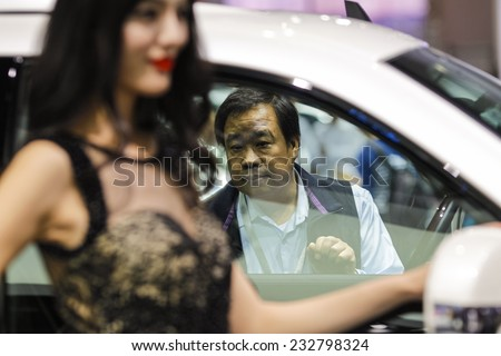 GUANGZHOU, CHINA - NOV. 21. 2014: Man looking in Cadillac Escalade car on the 12th China International Automobile Exhibition in Guangzhou, Guangdong province.