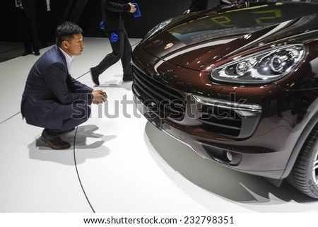GUANGZHOU, CHINA - NOV. 20. 2014: Man looking Porsche Cayenne on the 12th China International Automobile Exhibition in Guangzhou, Guangdong province.