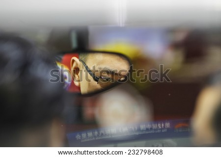 GUANGZHOU, CHINA - NOV. 20. 2014: Man seen in review mirror seating in car on the 12th China International Automobile Exhibition in Guangzhou, Guangdong province.