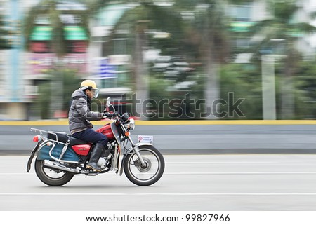 GUANGZHOU-FEB. 26, 2012. Man on a Honda motorcycle on Feb. 26, 2012 in Guangzhou. Honda was founded at 24 September 1948 and has been the world\'s largest motorcycle manufacturer since 1959.