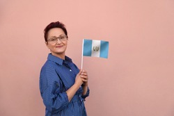Guatemala flag. Business woman holding Guatemalan flag. Nice portrait of middle aged lady 40 45 years old with a national flag over pink wall on the city street outdoors.