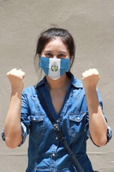 Guatemala flag on hygienic mask. Masked woman prevent germs and wear denim dress. Tiny Particle or virus corona or Covid 19 protection. Concept of Combating illness.