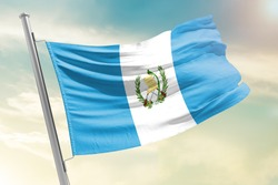 Guatemala national flag cloth fabric waving on the sky with beautiful sun light - Image
