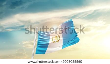 Guatemala national flag waving in beautiful clouds.
