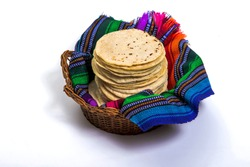 Guatemalan handmade corn tortillas inside a basket covered by traditional textile