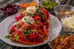 Guatemalan style enchiladas displayed to show their ingredients on a white plate.