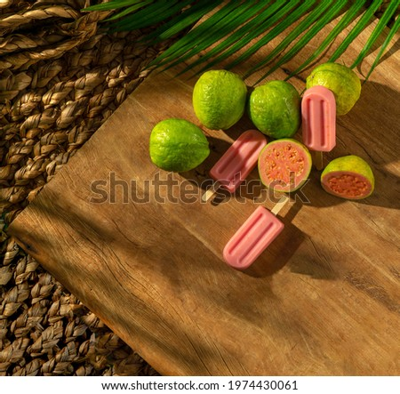 Guava Popsicle with grava fruits on a wood base, sunlight, palm leaf, top view Foto stock ©
