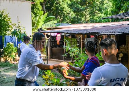 Guazacapan Guatemala 04-5-2019 latin teen giving mangoes to man in Guatemalan village #1375391888