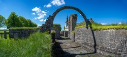 Gudhem Historical Monastery Ruin and Church with overgrown stone wall and arches