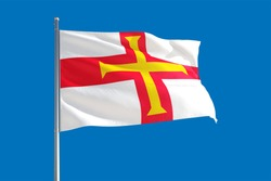 Guernsey national flag waving in the wind on a deep blue sky. High quality fabric. International relations concept.