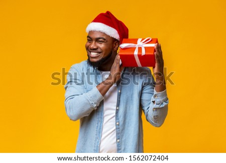 Guess what's inside. Happy black man in Santa hat shaking Christmas present, listening what rattles in gift box, yellow background
