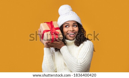 Guess What's Inside. Portrait Of Happy African American Woman Wearing Winter Hat Listening What Rattles In Gift Box. Curious Black Lady Shaking Christmas Present Isolated On Orange Background, Banner