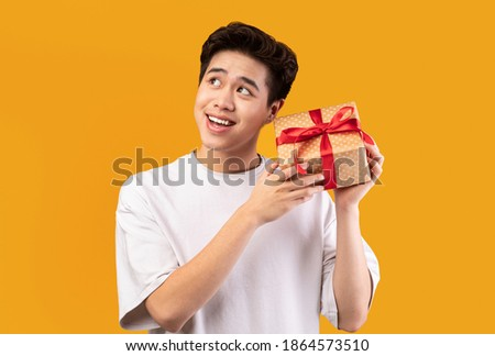 Guess What's Inside. Portrait Of Happy Asian Young Guy Listening What Rattles In Gift Box. Curious Man Shaking Present And Looking Away, Thinking, Isolated Over Orange Studio Background