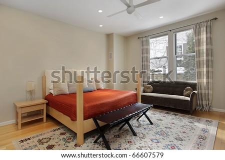Guest bedroom in luxury home with orange bedspread